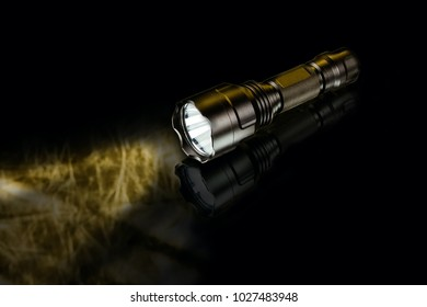 black anodized aluminium waterproof tactical flashlight on dark background