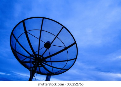 black antenna communication satellite dish over blue sky.
