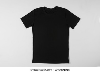Black apparel lying on a white background. Stylish tee-shirt with natural fabric. Simple and comfortable clothing concept. Designer tee-shirt made of cotton on light - Shutterstock ID 1990301015