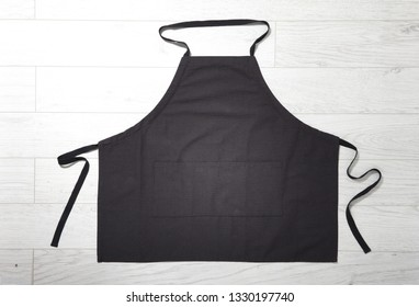 Black apron for kitchen top view on white wooden background. Mock up