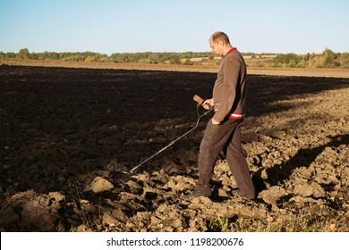 Black archaeologist with a metal detector in his hands walks across the field and searches for jewels and relics