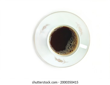 Black aromatic coffee with foam in an elegant porcelain coffee cup and saucer. White chinaware. White classic cup of hot coffee isolated on white background. Hot instant energetic drinks. Coffee break