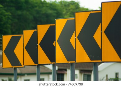 Black arrows on yellow traffic sign pointing left, Malaysia