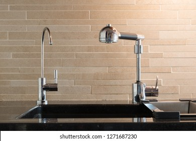 Black artifical stone countertop with black sink and two faucets