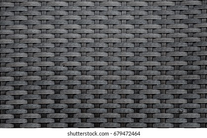 Black artificial rattan pattern. Background of basket structure close-up. Furniture backdrop