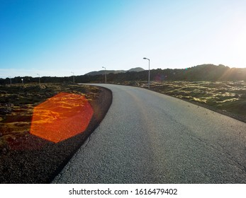 Black asphalt country road in a volcanic landscape in Iceland with moss. Backplate for car industry and cgi. Lense flare.