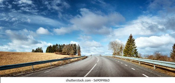 black asphalt road on sunny spring day. Panoramic view in early april