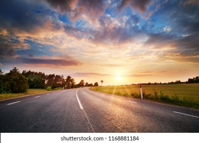 black asphalt road and white dividing lines at sunset