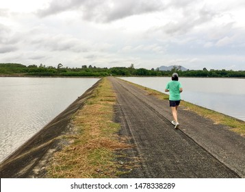 Black asphalt running track go straight pass the middle of the water reservoir on cloudy day and beautiful sky on background with copy space for text