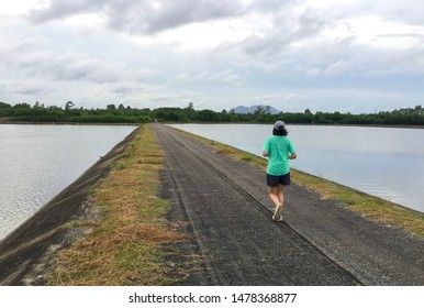 Black asphalt running track go straight pass the middle of the water reservoir dam in the evening on cloudy day and beautiful sky background with copy space for text on the left