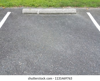 black asphalt with white lines and cement curb