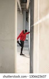 Black athlete stretching quadriceps during running urban workout.