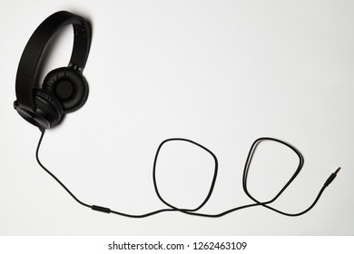 Black audio headphones with black cable isolated on white background
