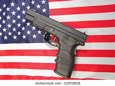 Black automatic pistol set against US flag