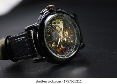 Black automatic self winding wristwatch with transparent sekeleton dial design on black leather background