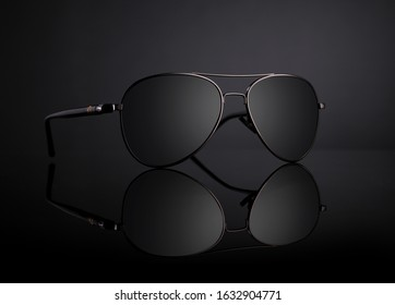 Black Aviator Sunglasses with Reflection on Black Background