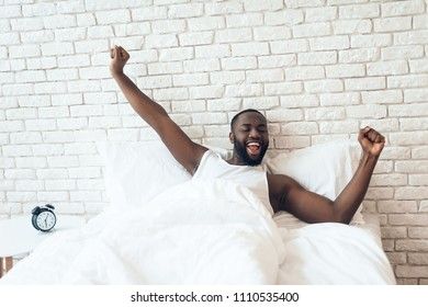 Black, awakened man is stretched out in bed. Early morning. Pleasant awakening. Waking up.