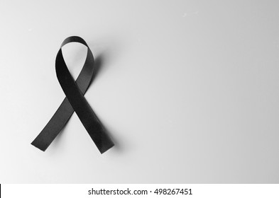 Black awareness ribbon on gray background. Mourning symbol, copy space.