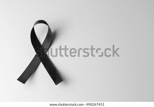 Schwarzes Sensibilisierungsband auf grauem Hintergrund. Trauerndes Symbol, Kopienraum.