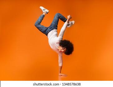 Black awesome man balancing on one hand on orange background