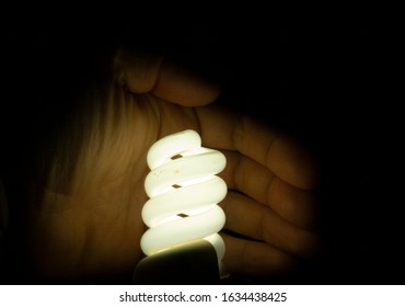 Black background about power saving with a glowing lamp and a hand