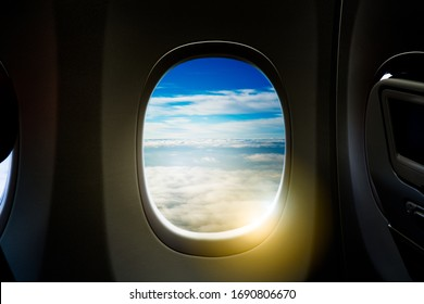 Black background with copy space look of window seat frame of airplane flight see view of clouds sky, wing travel during coronavirus risk crisis fall demand of flight cancel