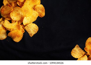 Black background with crisps. Potato crisps with salt, photographed from above.