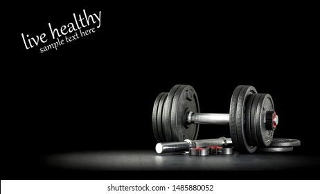 Black background of dark desk with dumbbells and free space for your text.