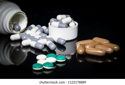 Black background with mirrored reflections Medicine , vitamins , pills , and drugs a daily dose of western medicine opioids and suicide is on the rise