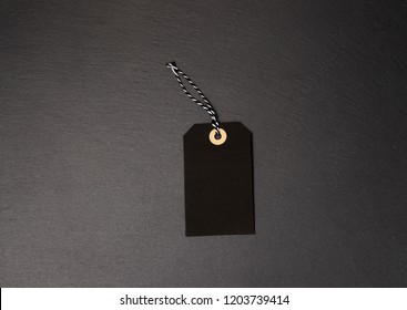 Black background and price label. Black Friday. Sales concept. Copy space.  Black paper label against a dark grey background. Black Friday shopping sale concept with ticket Sale tag close up