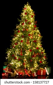 Black background with a shiny illuminated christmas tree isolated