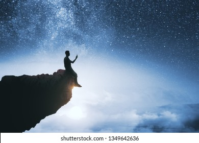 Black backlit young guy silhouette sitting on cliff edge and starry night sky cosmos background. Purpose and success concept