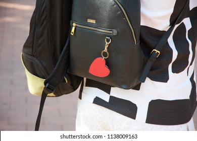 Black backpack and bag on woman's back while walking in the park with black and white dress. red heart keychain hanging from the bag.