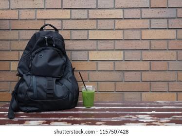 Black backpack and green tea brick break
