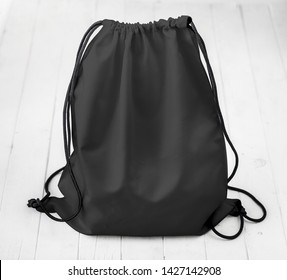 black backpack with strings on planked surface