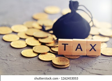 """Black bag for coins, golden coins, wooden letters """"tax"""". Tax concept. Selective focus."""