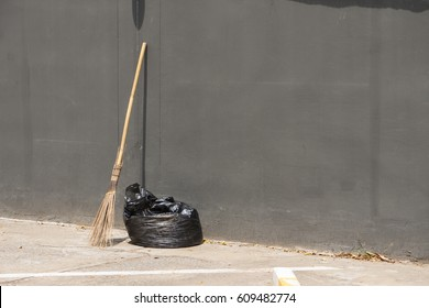 A black bag of garbage and old broom against a gray wall., with copy space for text.