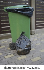 Black bag of trash with strings is near the green dumpster.