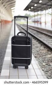 black baggage bag on platform at train station  - travel concept