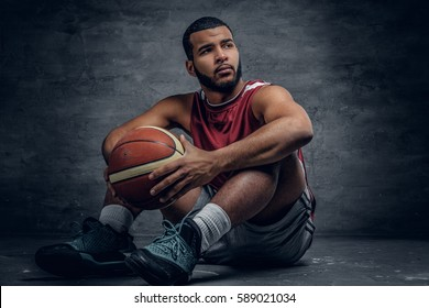 Black basketball player sits on a floor and holds a ball.