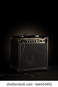 Black bass guitar amplifier whit a cord plugged in on black background