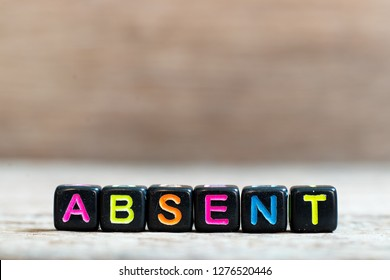 Black bead with color alphabet in word absent on wood background