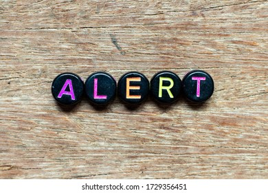 Black bead with color letter in word alert on wood background