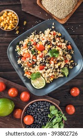 Black bean quinoa salad on rustic wooden background top view. Toned