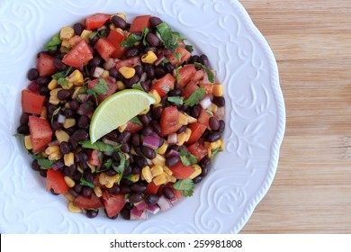 Black bean salad in white plate on wood background