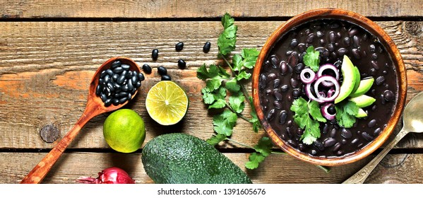 black bean soup or stew. Latin American or Mexican cuisine. stewed black beans served with avocado and red onion and cilantro. place for text. top view.