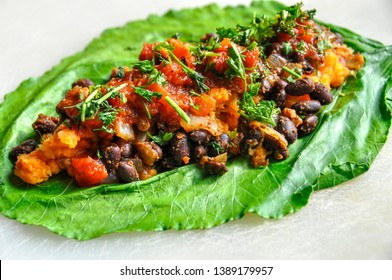 Black bean and sweet potato burrito wrapped in collard green leaf.  Vegan Mexican dish. Whole food, plant-based nutrition. Tex-Mex cuisine.