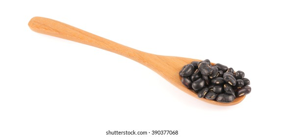 Black beans in wooden spoon isolated on white background