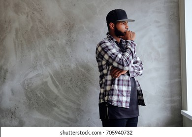 Black, bearded hipster male dressed in a fleece shirt and a cap, posing near window with natural light.