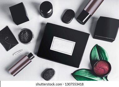 Black beauty box and various black and brown cosmetic product in jars and bottles with branding mock up.  Eye patch. Snail mucin or charcoal cosmetic set. Facial skin care . Blog promotion. Flat lay